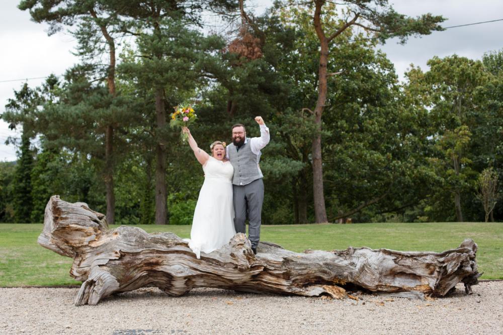 Alternative couple on log at Pimhill Barn Shrewsbury