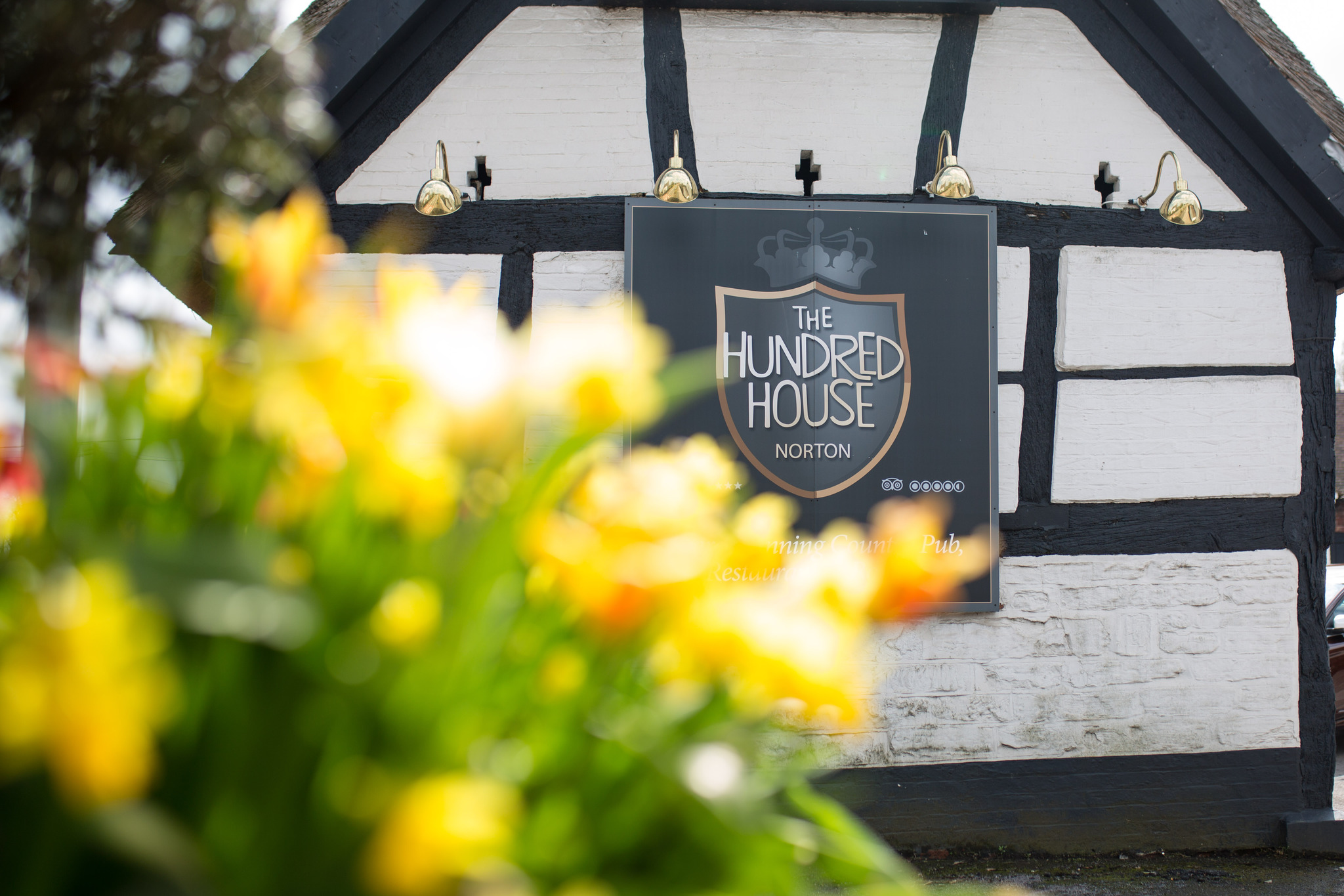 Hundred House Wedding Venue Exterior with daffodils and sign