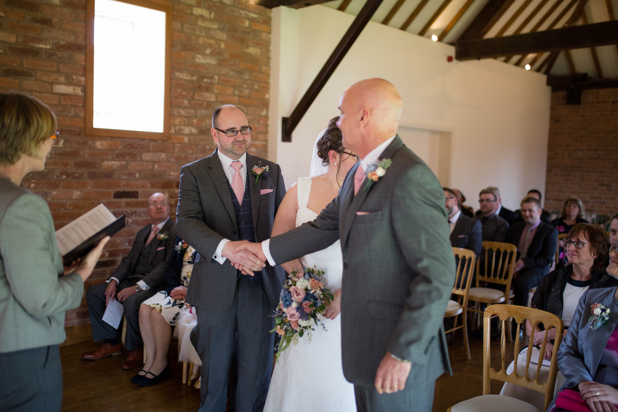 Groom and father of the bride handshake Delbury Hall indoor ceremony