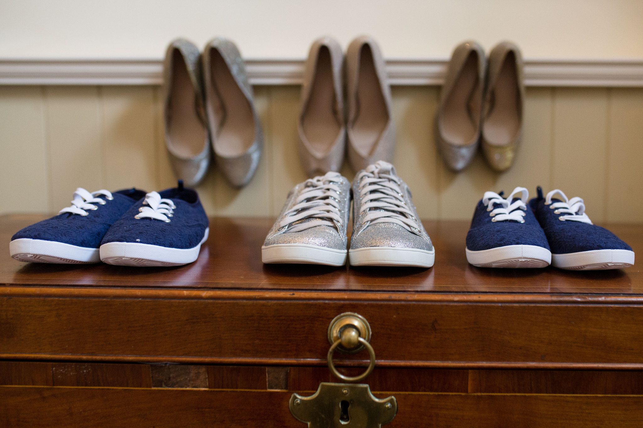 3 pairs of wedding converse with heels in background Delbury Hall Spring wedding