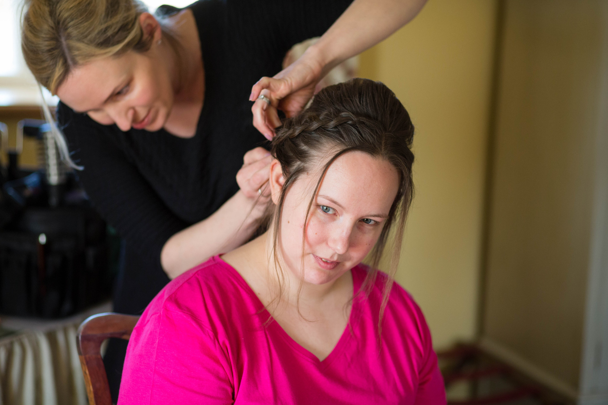 Bride in bright pink t shirt having hair done Delbury Hall