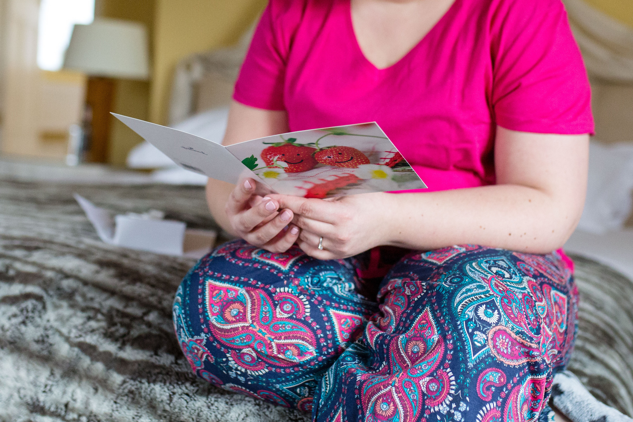 Bride in colourful pyjamas reading card with strawberries on the front