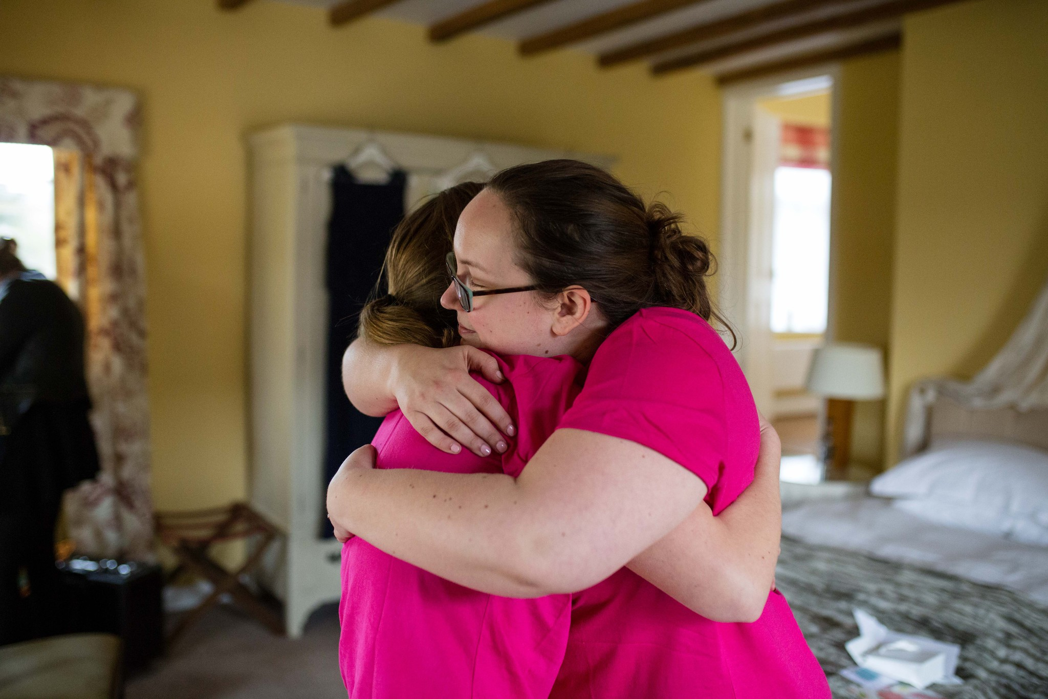 Bride and bridesmaid in bright pink t shirts hugging Delbury Hall