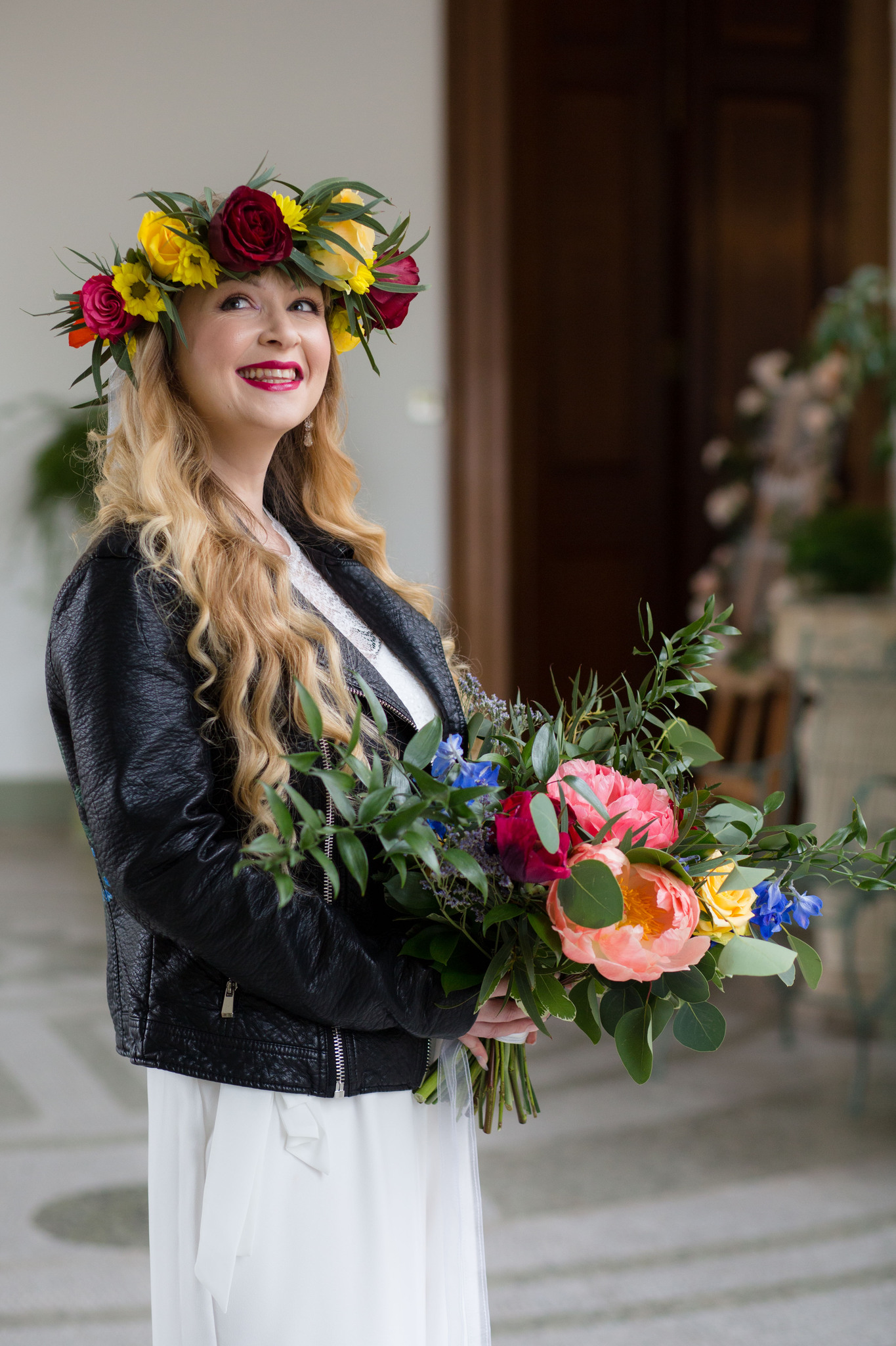 Boho Bride wearing flower crown and leather jacket and bridal jumpsuit
