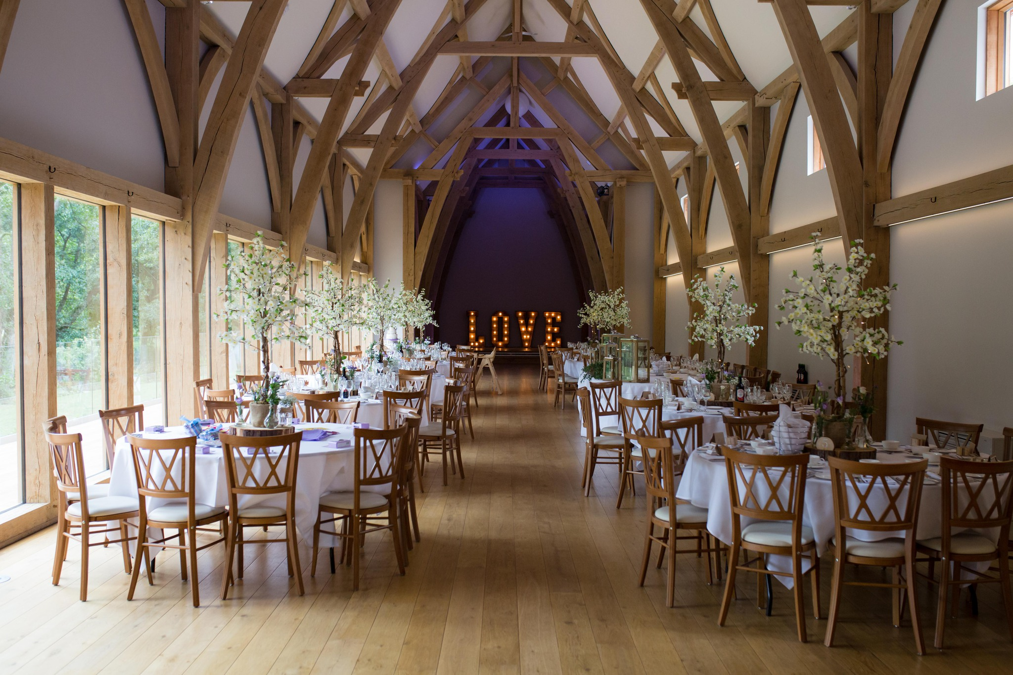 Mill Barns wedding venue interior dressed with blossom trees and light up love letters